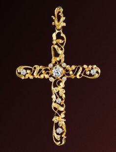 Diamond set cross with scrolls and flowers in yellow gold