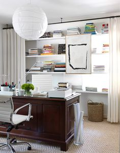 "wall-to-wall open shelves disguise an off-center window ""so I could center the desk in the room."" Curtains soften corners and hide everyday office clutter."