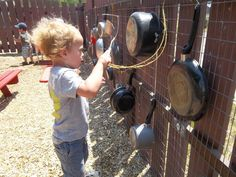 Toddlers explore with sounds in their outdoor classroom