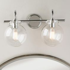 Retro Glass Globe Bath Light - 2 Light Retro and modern combine to bring clear light to your bath or vanity light. Polished chrome and clear round globes complement the detail of the metal. Available in a 2 or 3 light fixture, this is a great addition to a bathroom.