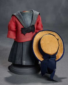 "Of navy blue serge, the sleeveless sailor dress top has all-around pleated skirt and center panel, and has pull-over red serge middy top with dart-shaped sleeves, blue middy collar. Along with a woven straw flat-top bonnet with navy blue band and streamers, and blue lined underbrim. For 11""-12"" doll. 3"" shoulder width. 4 1/2"" overall length. 2 1/4"" inside head width. Circa 1910."