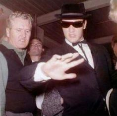 """Vernon and Elvis Presley are pictured at the Memphis Airport, Memphis, TN on Sunday, November 6, 1960. (Dee Stanley is also present.) Accompanied by Alan Fortas, Red West, Charlie Hodge and Joe Esposito E is on his way to Los Angeles for preproduction on 20th Century Fox's """"Wild In The County."""" Elvis shows the fans that his little finger on the right hand is OK. He had it broken during a game of touch football close to Graceland on October 16, 1960."""