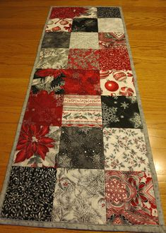 This very elegant table runner was made from the Holiday Flourish fabric line. The fabric is black, red, white, gray and silver metallic. The prints on the front include: poinsettias, ornaments, snowflakes, and leaves. This fabric was purchased at Missouri Star Quilt Company. This