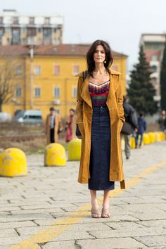 She looks fresh by keeping it simple. The long denim skirt paired with a busy yet not so mute top would look interesting on their own. However the yellow/brown/orange hue of the trench coat complements the outfit.
