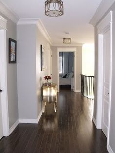 Grey walls, white trim, dark wood; like picture frame moulding on door and trim around door.