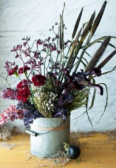 For a casual seasonal look, place an eclectic mix of deep-tone and long-lasting plants in a galvanized bucket. More Thanksgiving decorating: http://www.midwestliving.com/holidays/thanksgiving/easy-ideas-for-thanksgiving-decorating/page/12/0
