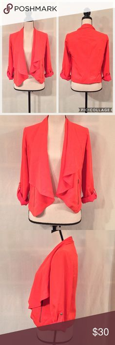 """Cartonnier Anthropologie draped travelogue jacket EUC. No stains or holes. Cartonnier (Anthropologie) draped """"Travelogue Jacket"""". A bright orange with a tiny bit of pink. Color most accurate in photo 4. Front vertical zippered pockets. Sleeves can rolled up and kept in place with buttoned tab. Cropped. 100% tencil (rayon). 100% polyester polka dot lining. Measurements (flat): shoulder width 15"""", bust 18"""", sleeves 17-21"""", length 20"""". Style 4115069699333. Dry clean only. No trades…"""