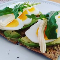 today's lunch crackers with pesto avocado egg mayonnaise and rocket salad on top. [23042304]
