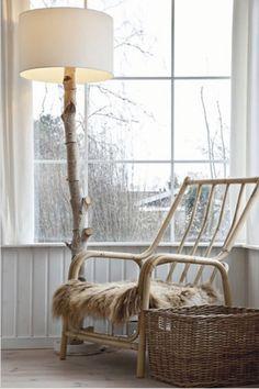 Leesplekje bij het raam met schemerlamp van boomstam en rotan stoel. Natuurlijk, eenvoudig en rustig.