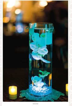 Turquoise dyed orchids in water with LED lights. Found on weddingbycolor.com