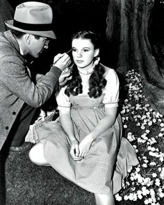 (Who wears that hat when they're applying makeup on set?) // Judy Garland during the filming of The Wizard of Oz