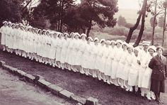 A black and white photo of nurses in white uniforms from the Marine Hospital standing in a line on the grass.