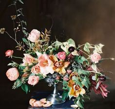 A winter centerpiece with peach Amaryllis, garden roses, and ranunculus, gold and wine-coloured orchids, plus an unruly assortment of foliage, ...
