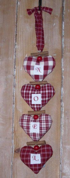 Four different red and white homespun fabric hearts with the letters N O E L attached to their fronts.
