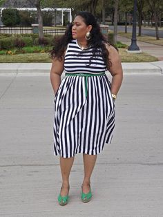 Plus size blogger Kiah rocking a thrifted navy and white striped dress with green accents.