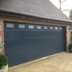 Anthracite Grey Flush Smooth Sectional Garage Door with windows glazing.  Automated and insulated.