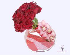 Akila. Arreglo de 12 rosas rojas que brotan de un florero de cristal con orquídea cymbidium rosas y con arena vibrante de colores.