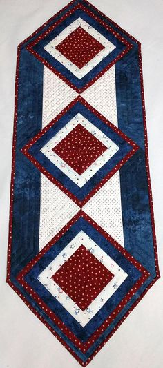 This unique quilted table runner will add a beautiful patriotic touch on holidays or every day of the year. The 15 x 43 table topper has center block that is a 3-dimensional candle mat that can be used flat for meals or holding a candle or vase all day. The centers of all 3 blocks are a dark red with stars, surrounded by a white patriotic fabric. The blocks are bordered with a dark blue and another border of the red stars. The blocks were then put on point, and a white with red dot fabric…