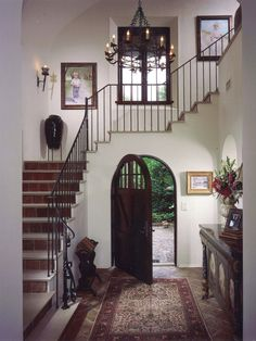 Old World Spanish-Style Entryway.  The arched doorway and wrought-iron chandelier give this entryway an Old World Spanish look. The neutral tones blend in with the outdoor surroundings, and the tile on the floor and stair risers integrate Spanish-inspired materials into the home. The staircase rises above the doorway, which is a clever way to create more open space in the home.