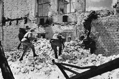 Soviet soldiers storming German troops hiding out in ruined buildings during the Battle of Stalingrad.  Of note is the man on the right standing on the back of his comrade to peer over the wall and take aim at German soldiers.    Stalingrad, 1942.