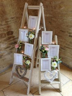 Table plan styling on wooden ladders with frames, candle votives & flowers at Kingscote Barn.  www.littleweddinghelper.co.uk