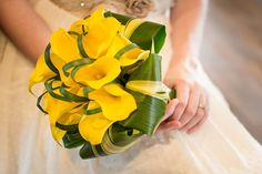 This modern swing to a bridal bouquet is striking with yellow callas, ti leaves and lily grass. photo courtesy of Jennifer Dixon of Spritied photography. Designed by www.wildroseevents.com #wildroseevents #wedding  #dallasflorist #modern #bridalbouqet #bearcreekranch