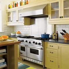 Yellow cabinets, white subway tile, stainless steel double oven/range
