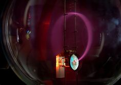 Beam of electrons moving in a circle in a magnetic field (cyclotron motion). Lighting is caused by excitation of atoms of gas in a bulb.