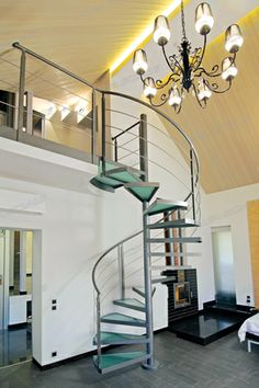 Iron spiral staircase. Embossed metallic enamel painting. Customized cylinder-shaped elements welded to steps covering iron solid newel. Diameter from 100 to 160 cm. Private house in  St. Petersburg RUSSIA