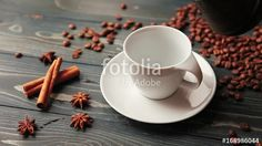 Pouring homemade coffee into a cup. Coffee beans, cinnamon sticks and a crumb on a wooden table
