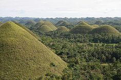 See the chocolate hills...because I remember learning about them when I was little.