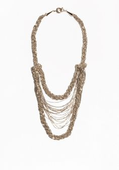 Interlacing strands of bar chain cascade down the front of this lavish necklace finished with a soft gold tone.