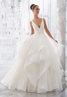 "Light and Airy, this Stunning Flounced Organza Ball Gown with Wide Horsehair Edging Features a Plunging V-Neck and Open V-Back. Illusion Insets Along Sides . Available in Three Lengths: 55"", 58"", 61"". Colors Available: White, Ivory, Ivory/Stripe."