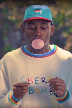 Tyler The Creator wearing Golfwang Fila Cherry Bomb Hat, Golfwang Cherry Bomb Sweater