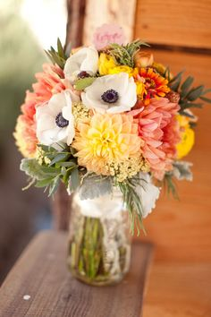 Bouquet of white amenomes, peach dahlias, coral dahlias, assorted zinnias, rosemary, yellow ranunculus, yarrow dusty miller, sahara roses, garden yarrow, and lavender.