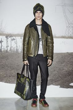 A look from the #CoachMens2015 presentation: the Military Shearling B3 Flight Jacket, Grey Heather/Black Ringer T-Shirt, Black Wool Trousers, Military Wild Beast Beanie, Feather Necklace, Black Cord Pouch, Wild Beast Shearling Lo-Top and Wild Beast Pebbled Manhattan Tote