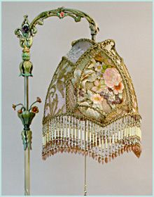 Ornate, intricately hand painted 1920s tole bridge lamp with dimensional flowers holds a Spring Garden shadowbox shade in soft, romantic pastel tones of pink, green, butter yellow, peach and lavender. Antique hand-dyed cut velvet and gold metallic lace overlay the panels and the shadowbox is filled with rare, heavy, luxurious 19th Century French floral embroidery and Victorian era gossamer gold mesh.