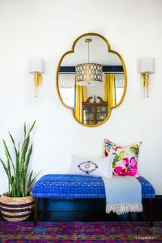 Colorful entryway with a Moroccan style mirror, bright blue bench, pillows, sconces and plants.