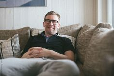 Middle-age man sitting in a sofa with a smile by Jonas Räfling