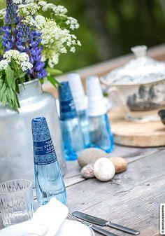 """Avaruusasema-blogin Tia ja Mikko kattoivat kesäpöytään Spring Aqua Premium -pullot. """"Vanhat astiat luovat ihan oman tunnelmansa ja ne sopivat täydellisesti mökille. Spring Aqua Premium -vesipullot ovat siroja ja etiketit niin kauniita, että ne voi kattaa suoraan pöytään."""""""