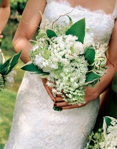 The bridesmaids will carry loose, natural, hand-tied bouquets of white-green Queen Anne's lace and a mix of foliages including magnolia leaves wrapped in blush ribbon with the stems showing.