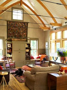 This is a great room, the arched ceiling is fantastic. I'd change out the beams with Barn Wood, and put a Cathedral Stained Glass window in the top center of the room