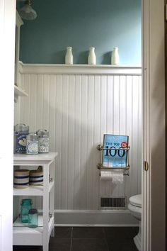 "A small powder room is conveniently located off the mudroom. White antique milk bottles rest on the ledge of wainscoting set high on the wall.     When it came to flooring, Lenore prioritized practicality without sacrificing flair. ""These slate-looking tiles are actually porcelain and are amazingly durable. You could drive a car over them,"" she says. ""My three boys give them quite a beating, and they are still in great condition.""    Paint color: Glenwood spring, MAB"