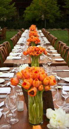 Floral Design by Erica Rose. (orange, tulips, long natural wood tables, outdoors)