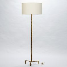 French Mid Century Faux Bamboo Brass Floor Lamp  --  Circa 1940s French floor lamp with a brass base sculpted in the form of slender, triple bamboo strands. Tri foot base and off white fabric drum shade. Measurements shown include shade. New wiring for US electrical standards.  --   Item:  7202  --  Retail Price:   $1895