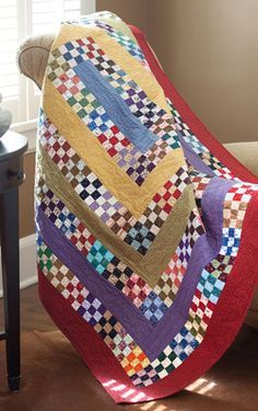 Nine Patch Square Dance features nine patch quilt blocks layered with solid borders. Designer Lynn Roddy Brown traded fabric scraps and strips to obtain a variety of colors and prints for her striking quilt. Using strip sets helps obtain accurate measurements so all pieced Borders fit properly.