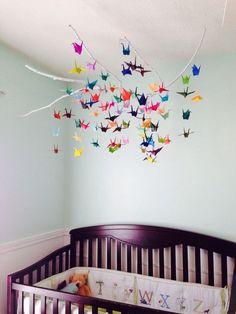 bunte Origami Kraniche schweben über dem Babybett
