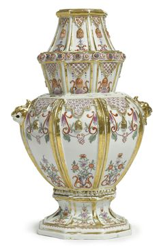 A RARE DU PAQUIER PORCELAIN POLYCHROME OCTAGONAL VASE  CIRCA 1725-30 painted on each gilt-edged side with a floral motif and scrollwork beneath a molded gilt-edged and tasseled diaperwork lappet, applied around the neck with a border of colorful flowerheads and affixed on either side with a gilt grotesque mask handle