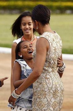First Lady Michelle Obama receives loving greeting from her daughters.