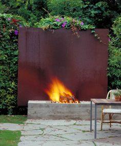 Cortenstahlwand hinter der Beton-Feuerstelle